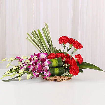 Brightly Blanc - Basket arrangement of 10 Red Carnations & 4 Blue orchids.
