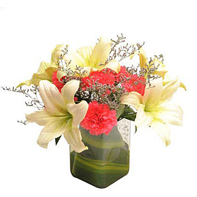 Glass vase arrangement of 6 dark pink carnations, 2 white asiatic lilies, seasonal filler and draceane leaves