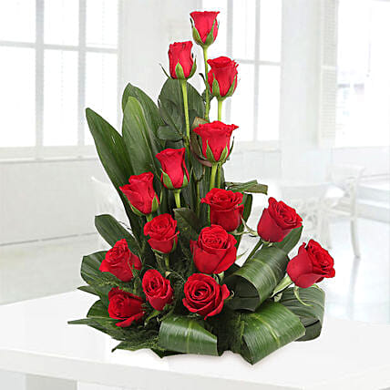 Cane basket arrangement of 15 red roses, draceane leaves and seasonal filler flowers gifts